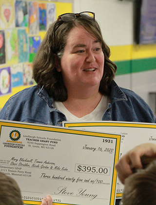 Teacher holding two foundation grant checks