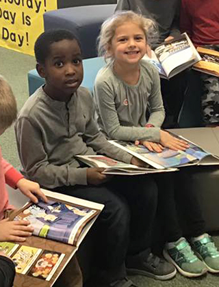 Two kindergarten students pose for photo while reading in the library