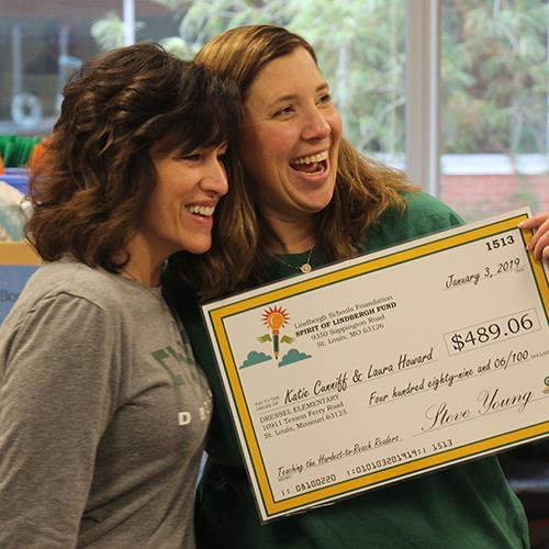 Teachers smiling while holding foundation grant check