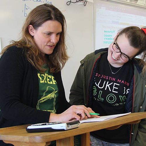 High school teacher helping a student