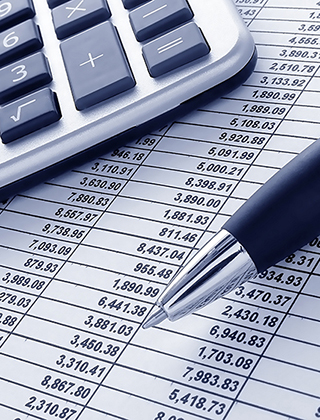 A calculator and pen on financial spreadsheets