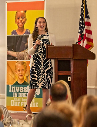 High school teacher speaks to audience at foundation event