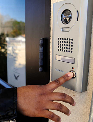 Close up of a hand pressing the buzzer at a school's main entrance
