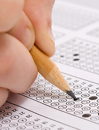 A student using a pencil to complete a multiple choice answer sheet