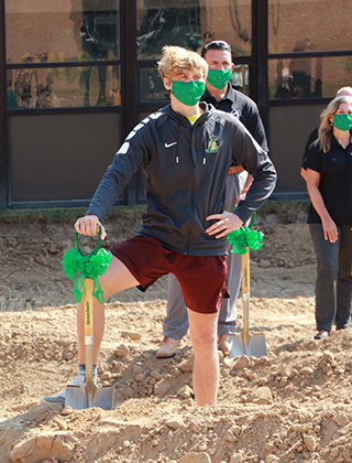 Student standing on a pile of dirt with a shovel
