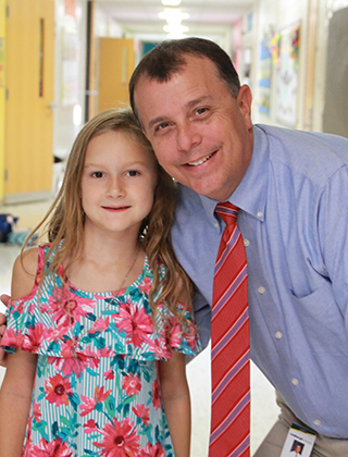 Superintendent Dr. Tony Lake poses for a picture with an elementary school student